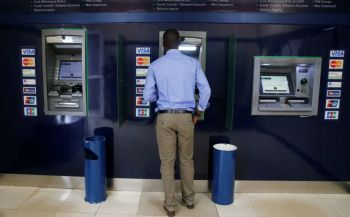 A customer uses an ATM outside the banking hall at the Kenya Commercial Bank, Kipande house branch in Nairobi